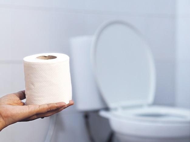 Рука держит ткань над размытым белым туалетом Premium Фотографии