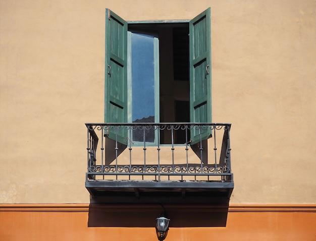 Деревянное окно на оранжевой стене с балконом Premium Фотографии