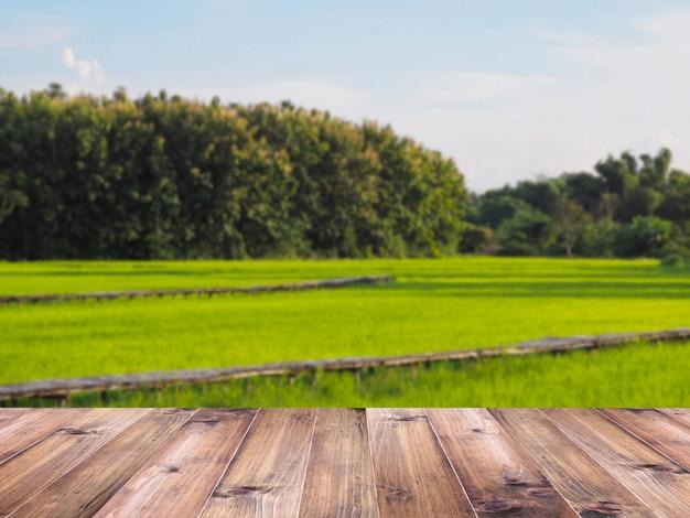 Верхняя часть деревянного стола над зеленой предпосылкой поля риса. Premium Фотографии