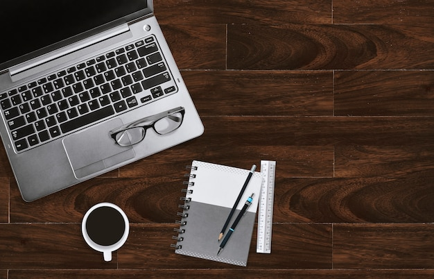 ホームオフィスデスクトップ職場で、眼鏡とコピースペースのあるノートパソコンを備えたノートパソコン。 Premium写真