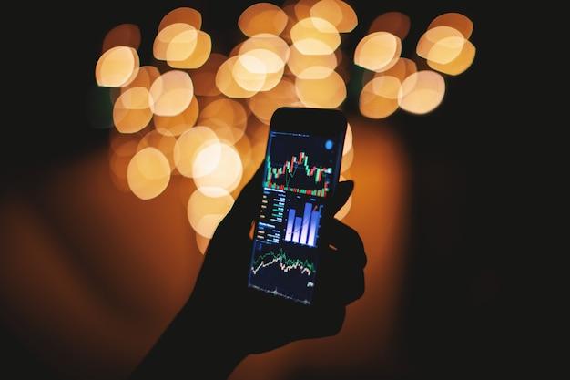 Силуэт руки, держащей смартфон с биржевой дисплеем с светлом фоне Premium Фотографии