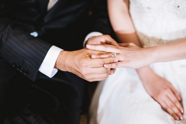 結婚指輪を花嫁の指に置く新郎 Premium写真