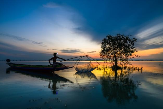 日の出と魚を捕る船の漁師 Premium写真