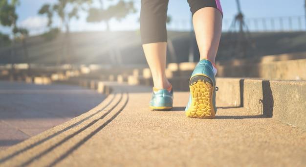 トラック上のフィットネス女性ランナーの足は、スポーツの靴に焦点を当てます。フィットネスとトレーニングウェルネスのコンセプト。 Premium写真