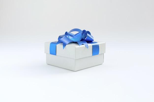 Подарочная коробка с бантом и лентой синего цвета на белом фоне Premium Фотографии