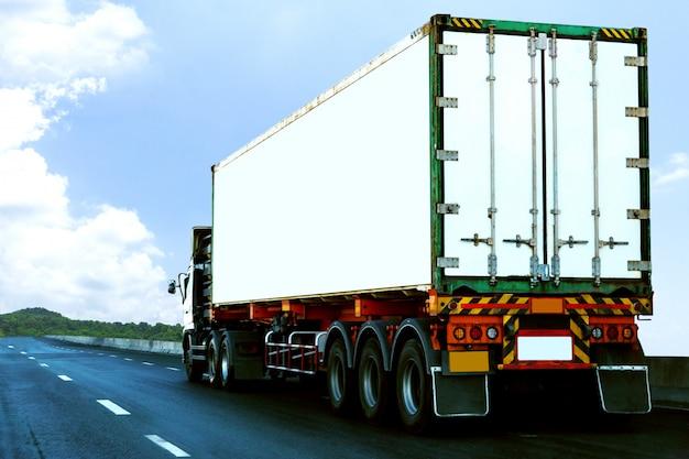 コンテナー、輸送の概念と高速道路道路上の白いトラック。インポート、エクスポート物流産業輸送アスファルト高速道路再び青い空に陸上輸送 Premium写真