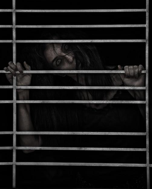 暗いケージのポンドルームで所有している女性のホーストハロウィーンのホラーシーン Premium写真