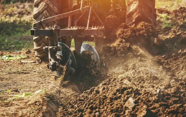 種まき用の土地を準備するトラクター耕起フィールド Premium写真