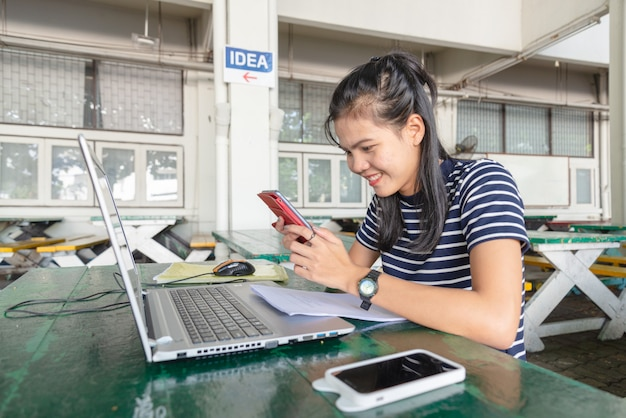 アジアの女性は、大学周辺のテーブルで携帯電話とノートブックを使用しています。彼女は仕事に満足しているようです。ソーシャルメディア中毒者の概念。 Premium写真
