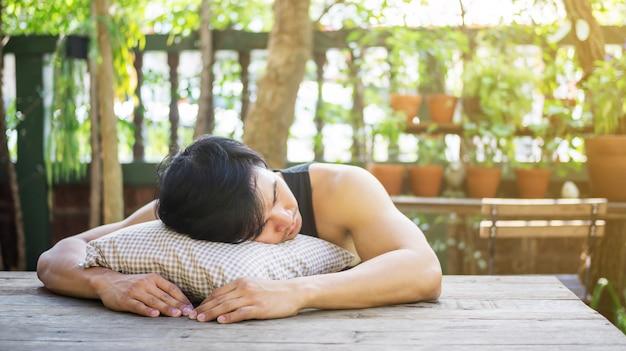 Молодой азиатский человек спать в саде. Premium Фотографии