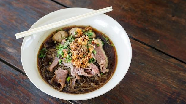 木製の背景(タイの麺)に豚肉の麺。 Premium写真