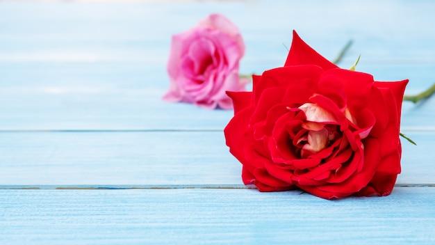 青い木製のテーブルの上の赤いバラとピンクのバラ。 Premium写真