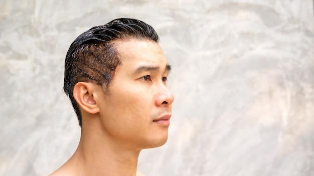 アジアの男性は、灰色の背景に彼の髪の色を染めます。 Premium写真