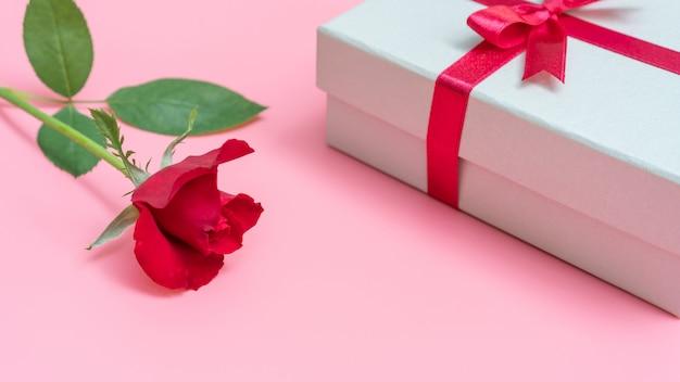 ピンクの背景に赤いバラとギフトボックス。 Premium写真