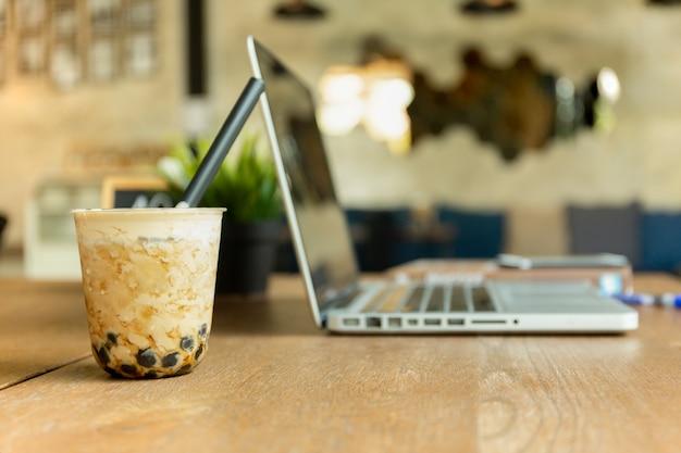 パールミルクアイスカフェで木製のテーブルの上のラップトップとお茶。 Premium写真