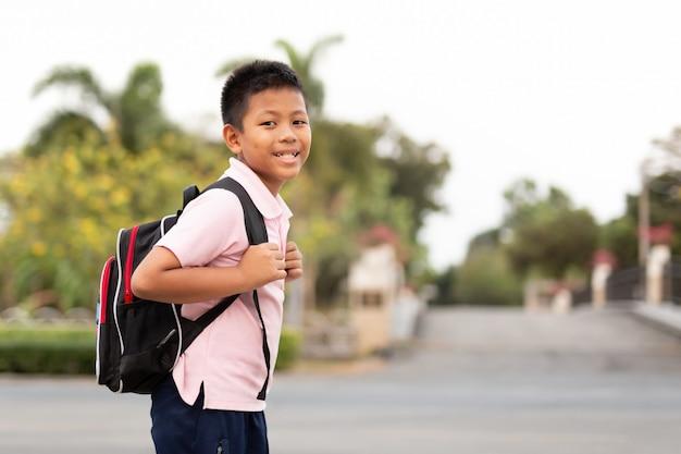 家に戻って歩いてバックパックと制服を着た幸せなアジアの学校の男の子。 Premium写真