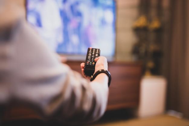 テレビを見るためにリモコンを使って手。 Premium写真