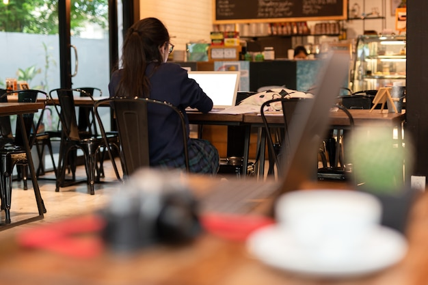 若い女性学生がカフェでノートパソコンでの作業します。 Premium写真