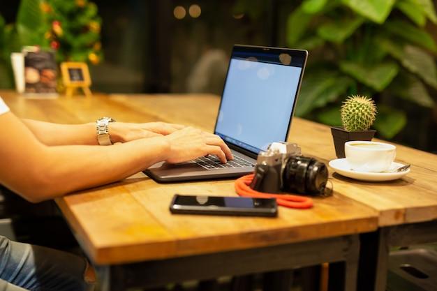 カメラとテーブルの上のコーヒーとラップトップに取り組んでいる男性の手。 Premium写真