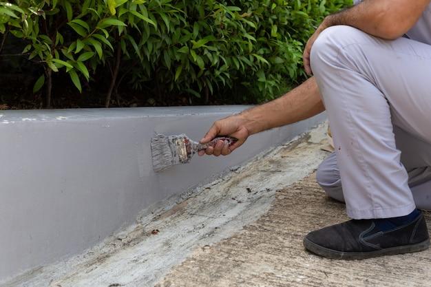 男労働者が絵筆でコンクリートの壁を塗る。 Premium写真