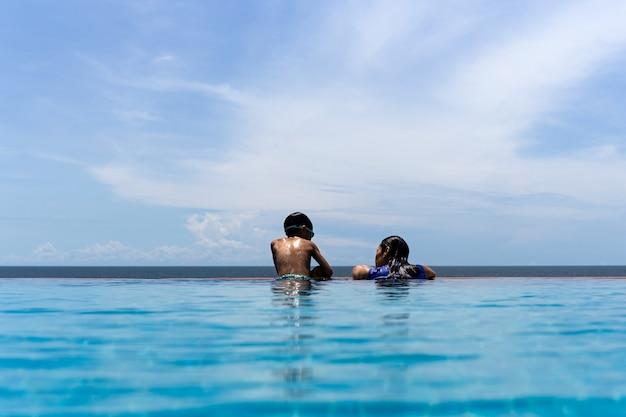 母と幼い息子は、夏休みに海を見渡すスイミングプールでリラックスします。 Premium写真