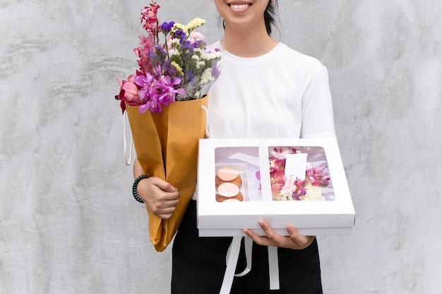 花とギフトボックスを保持している陽気な女性の肖像画。 Premium写真