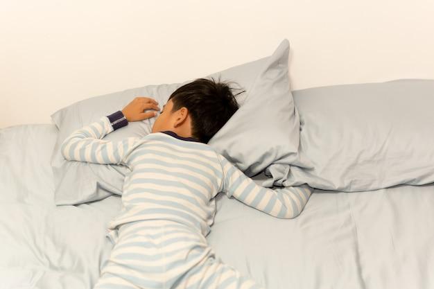 自宅の枕の下で頭をベッドで寝ている少年。 Premium写真