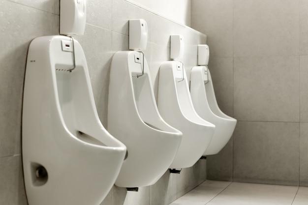 男性の公衆トイレで並んでいる白い便器。 Premium写真