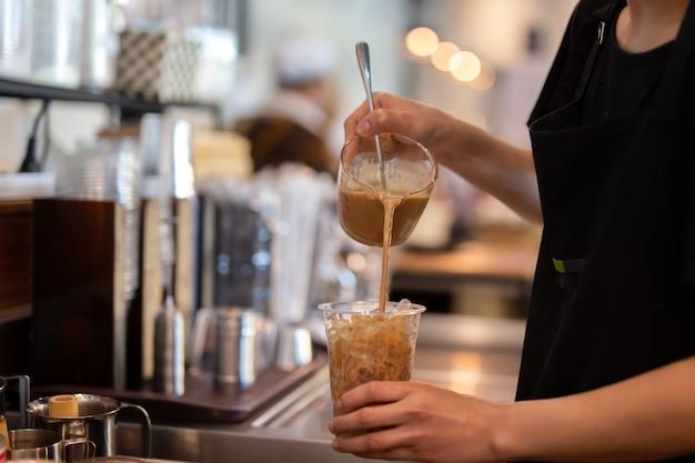 バリスタコーヒーショップでテイクアウトグラスにコーヒーを注ぐ女性バリスタ。 Premium写真