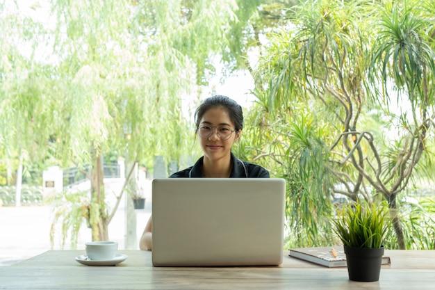テーブルの上のコーヒーカップとラップトップを使用して笑ってメガネアジア女性 Premium写真