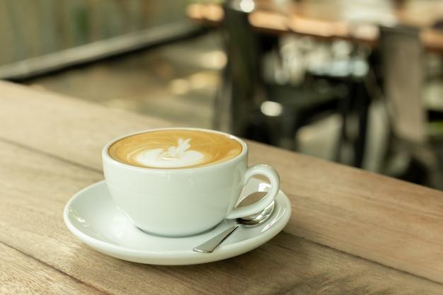 Чашка кофе с пеной на деревянном столе в кофейне. Premium Фотографии