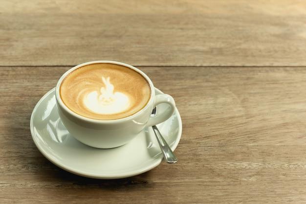 Чашка кофе с пеной на деревянном столе. Premium Фотографии