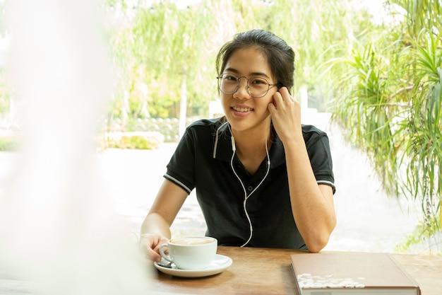 アジアの女性学生がカメラ目線のイヤホンでラップトップに取り組んでいます。 Premium写真