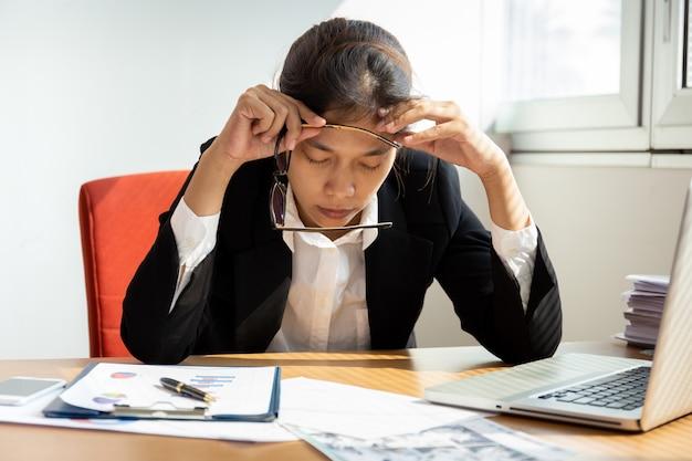 Коммерсантка отдыхая руки на голове с глазами близко на столе работы в офисе. Premium Фотографии