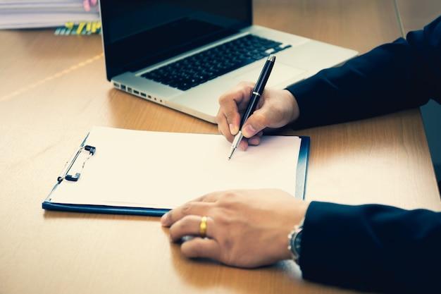 Форма контракта успешной руки дела подписывая на деревянном столе в офисе. Premium Фотографии