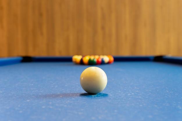 ビリヤードプールゲーム。青いテーブルの背景にセット色ボールとスポットの白いボール。 Premium写真