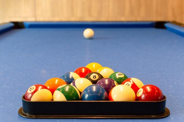 数字の付いたマルチカラーのビリヤードボールは、テーブルの青い布の上の三角錐にあります。 Premium写真