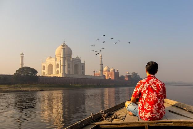 飛んでいる鳥と木製のボートからタージ・マハルに沈む夕日を見ている男。 Premium写真