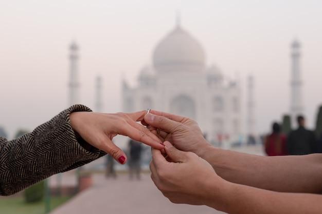 バックグラウンドでタージ・マハルと彼の妻の指に婚約指輪をかぶる人。 Premium写真