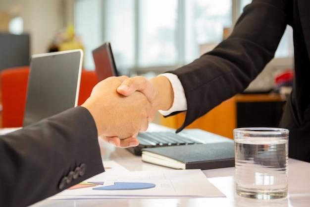 オフィスでの取引後の成功したビジネスマンハンドシェイク契約。 Premium写真