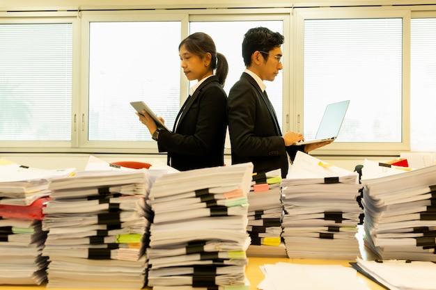 紙の山で背中合わせに立っているビジネスマンは、フォアグラウンドで動作します。 Premium写真