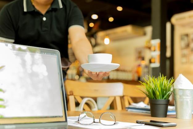 男性のウェイターがカフェで作業テーブルの上のノートパソコンとメガネとコーヒーを提供しています。 Premium写真