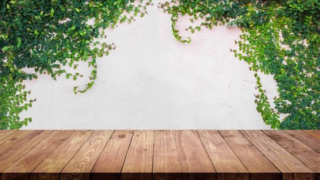 ツタの空の木製テーブルは、セメント壁の背景に残します。 Premium写真