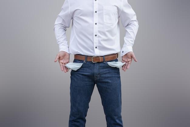 男は壁の背景に彼の空のポケットを見せて。 Premium写真