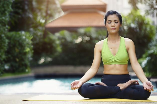 ヨガを練習している女性は、プールの近くに座っている蓮の姿勢で瞑想します。 Premium写真