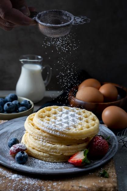 Домашние бельгийские вафли с черникой и клубникой, поливая сахарной пудрой. Premium Фотографии