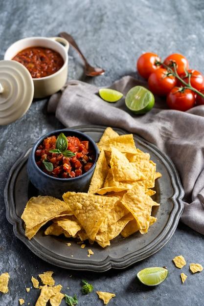 パーティー、メキシコ料理のナチョストルティーヤチップスとトマトのディップサルサのための軽食。 Premium写真