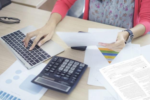 Женщина бухгалтер работает на счетах планирования налоговых доходов в бизнес-анализа Premium Фотографии