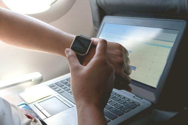 手首にスマートな腕時計を持つ男性の手。カレンダーイベントプランナーを使用した計画議題とスケジュール Premium写真