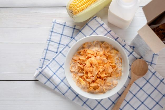 ボウルに牛乳とシリアルのコーンフレークボックス、エネルギーの健康、朝食の毎日の食事とコーンフレーク。コピースペースのトップビュー。 Premium写真